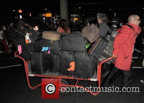 Boyband One Direction, arrives back home to England,...