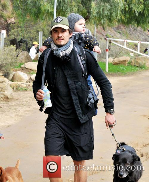 Orlando Bloom carries his son Flynn on his...