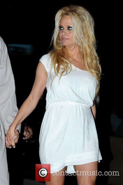 Pamela Anderson holding hands with a male friend...