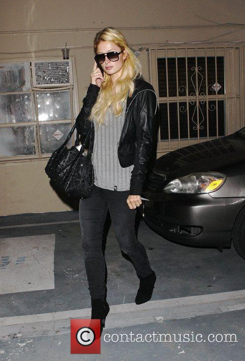 Paris Hilton talks on her phone as she...