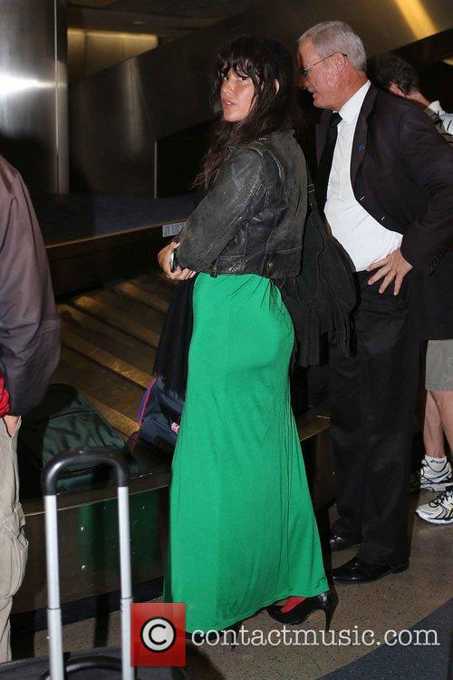 Arrives at LAX Airport wearing a green dress...
