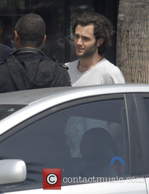 Penn Badgley talks to a friend in Venice...