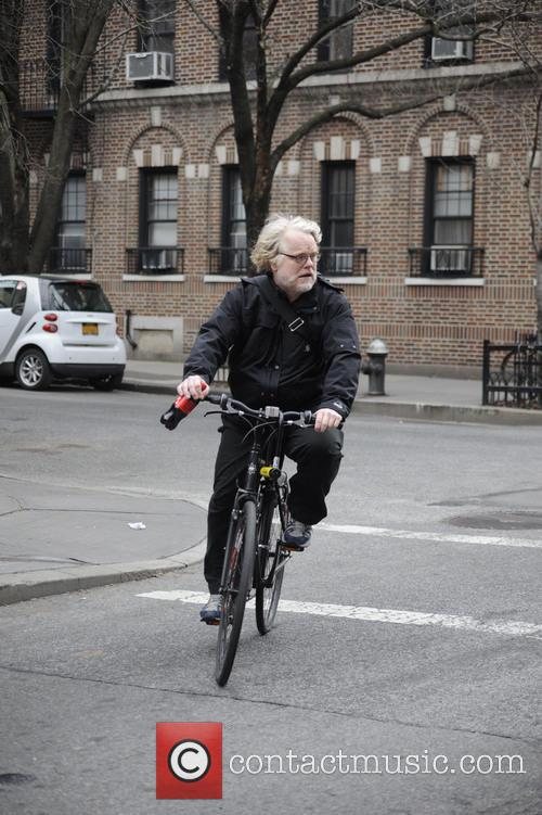 Philip Seymour Hoffman riding his bike while holding...