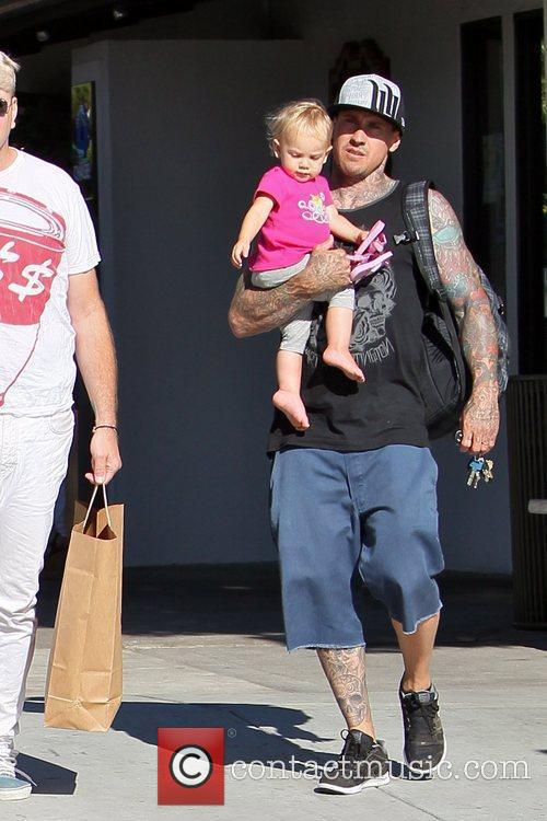 Carey Hart carries his baby daughter as they...