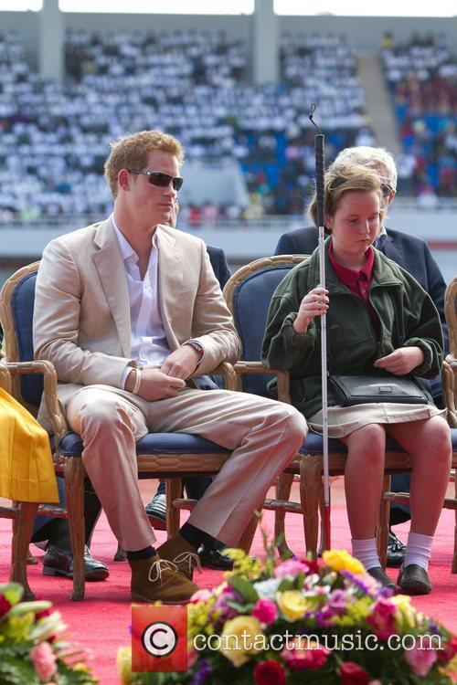 Prince Harry sits with blind student Anna Albury,...