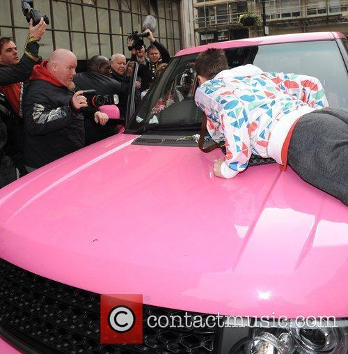A man jumps on the bonnet of Katie...