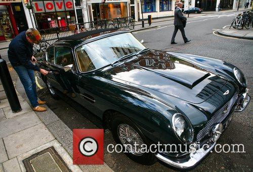 Chris Evans gets into his Aston Martin as...