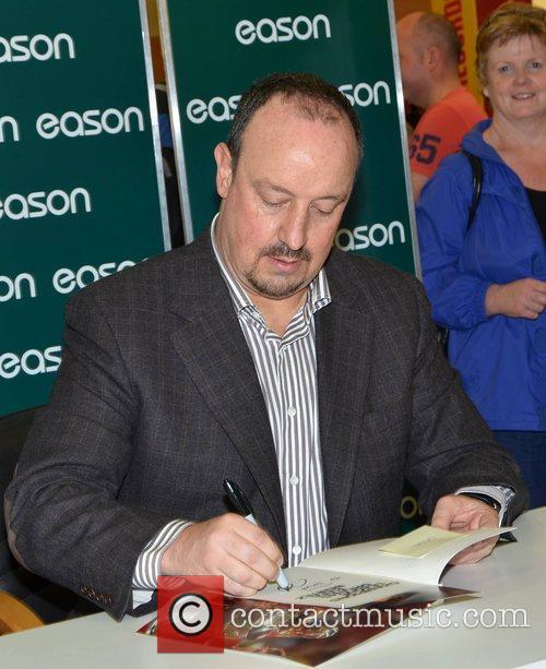 Signs copies of his book 'Champions League Dreams'...