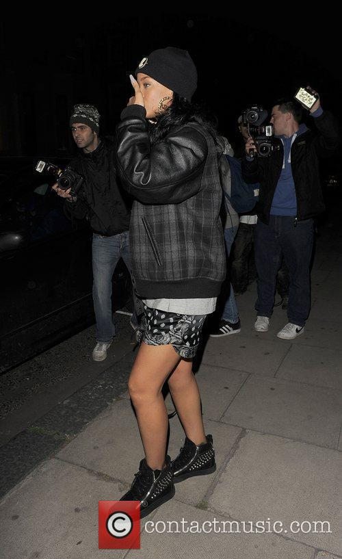 A camera-shy Rihanna leaving a recording studio late...