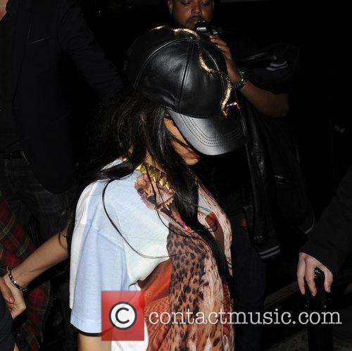 Rihanna hides from the cameras as she leaves...