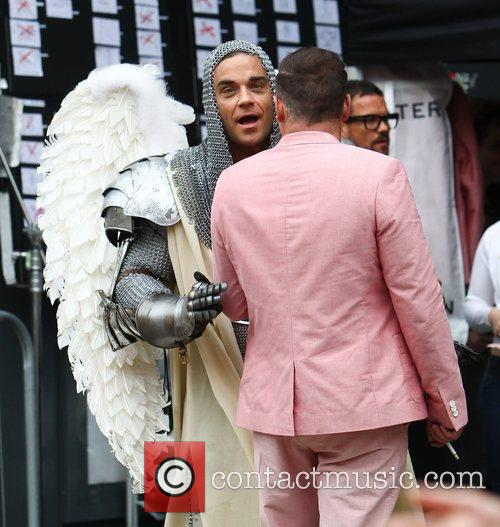 Robbie Williams talks to his stunt double during...