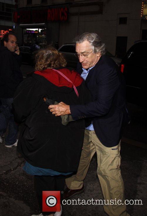 Actor Robert DeNiro avoids the press by maneuvering...