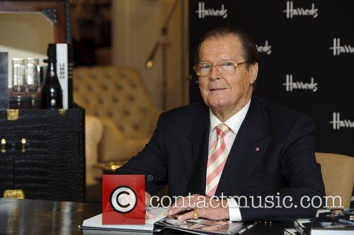 sir roger moore signs copies of his 4123930