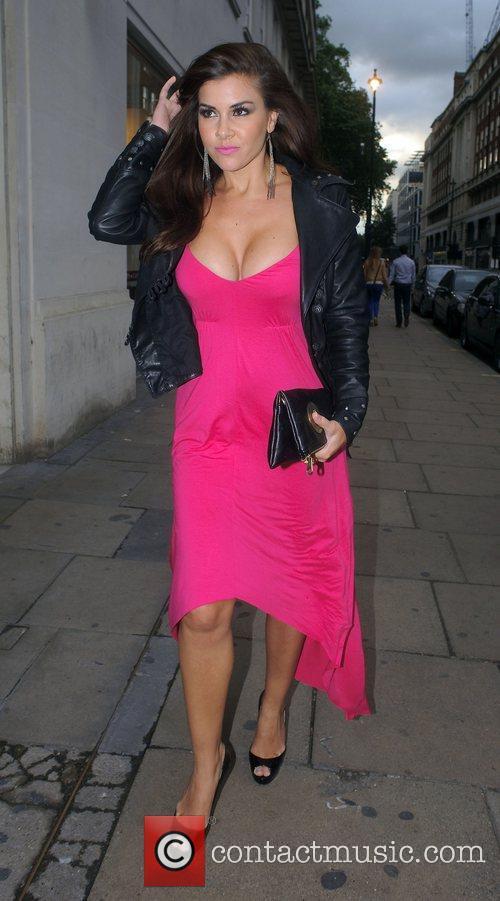 Wearing a low cut dress as she arrives...