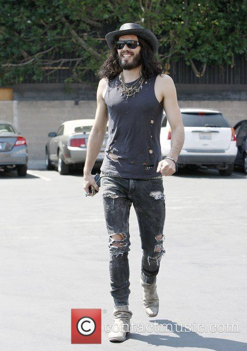 Russell Brand wearing ripped jeans and boots and...