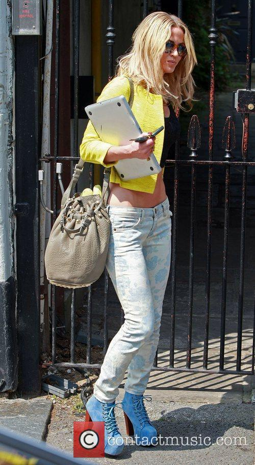 Sarah Harding  leaving her house carrying her...