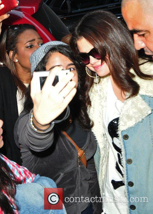 Is surrounded by fans and paparazzi outside her...
