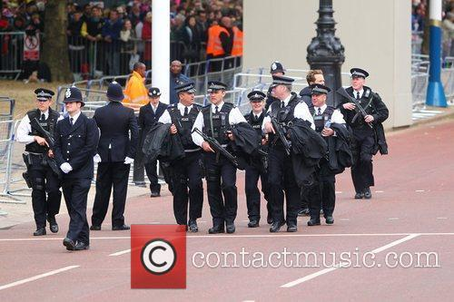 Armed police officers walk along The Mall ahead...