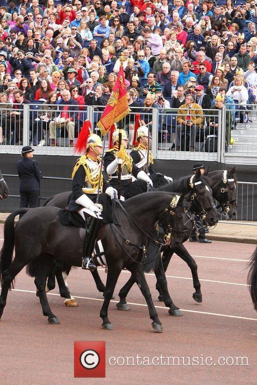 Royal guards on horses walk along The Mall...