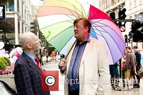 Holding a rainbow coloured umbrella as he talks...