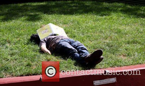 Student taking a nap, on the lawn at...
