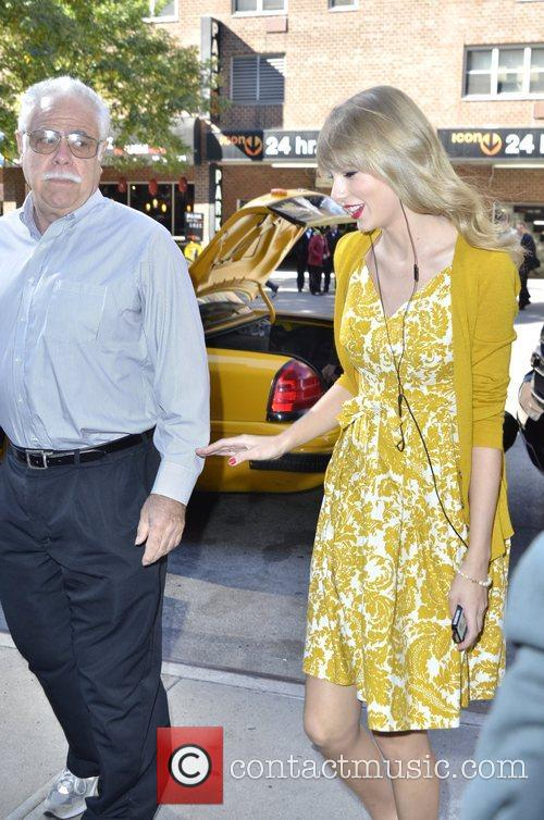 taylor swift wears headphones while returning to 5938382