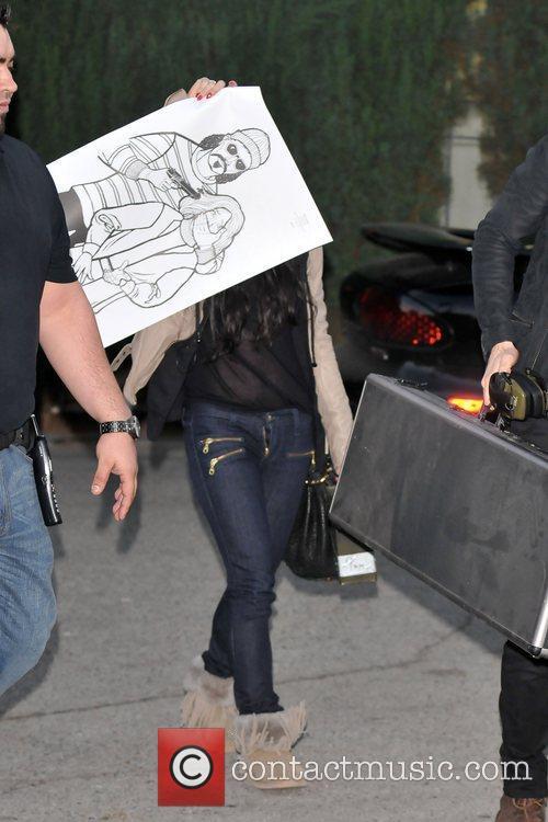 Vanessa Hudgens hides from paparazzi as she exits...