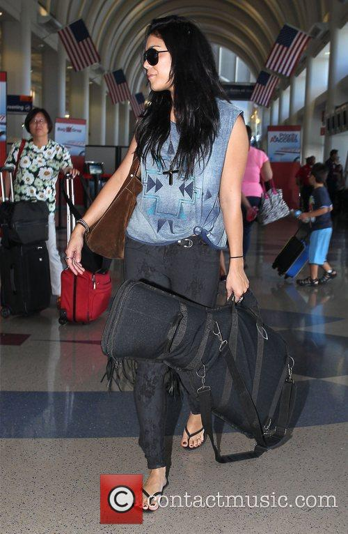 Arrives at LAX Airport, carrying her guitar in...