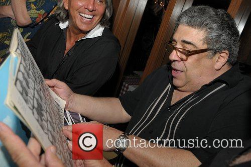 vincent pastore looking at photo albums which 3714035