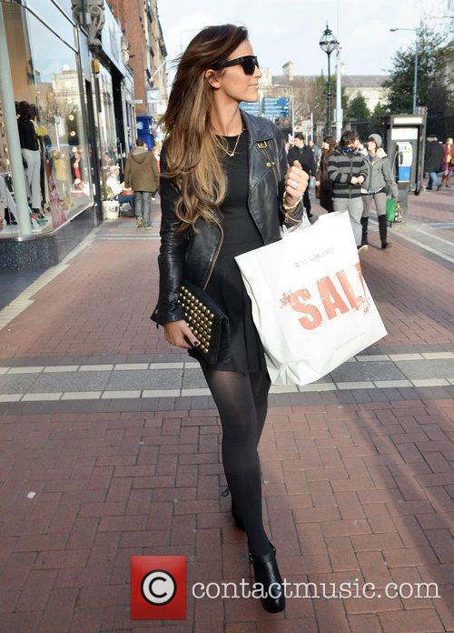 Shows off her engagement ring while shopping on...