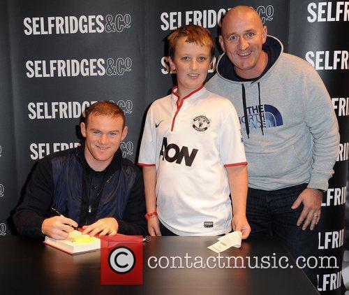 Signing copies of his book 'Wayne Rooney: My...