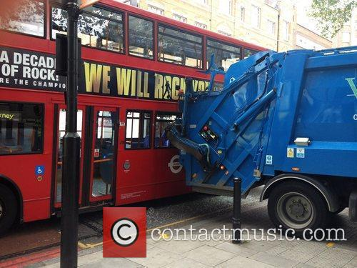 A rubbish truck backs into a double-decker bus...