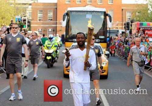 Torchbearer 109 Will.i.am carries the Olympic flame through...