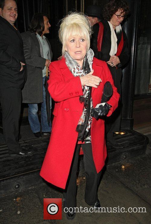 Barbara Windsor wearing a scarlet red coat leaves...