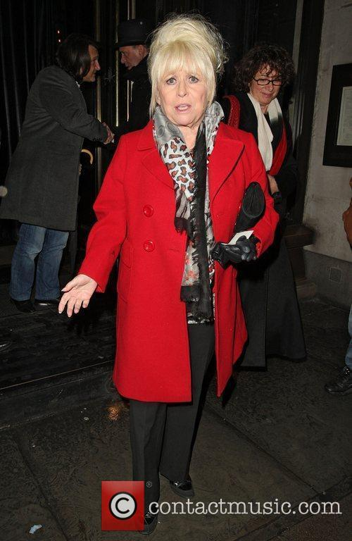 Barbara Windsor wearing a scarlet red coat leaves...