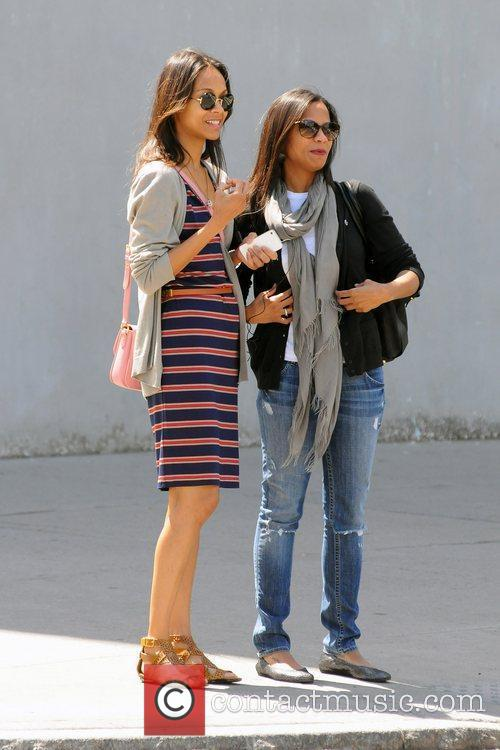 Zoe Saldana wearing a striped dress while out...