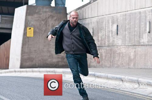 Jason Statham playfully tries to grab a camera...
