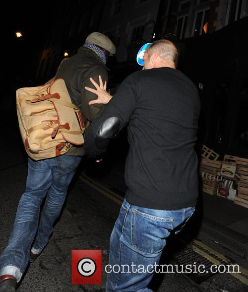 Jason Statham playfully tries to grab a camera from the hands of a paparazzi photographer