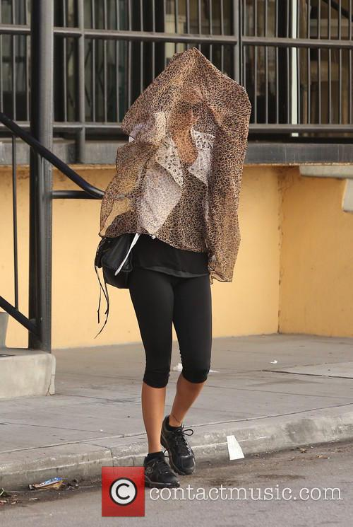 Nicole Richie covers her face with a scarf...