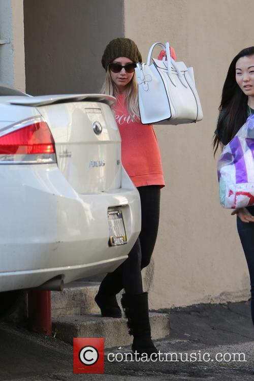 Ashley Tisdale covers her face while shopping