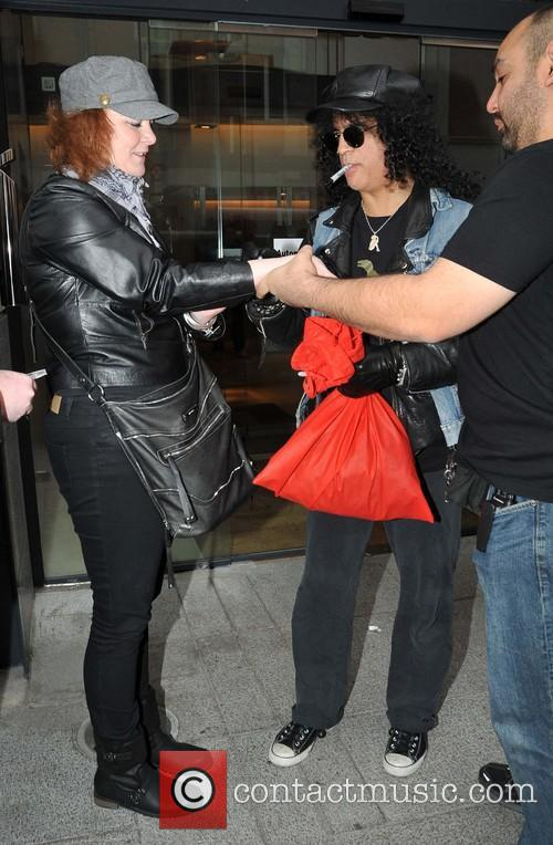 Guitarist Slash is seen greeting fans outside the...