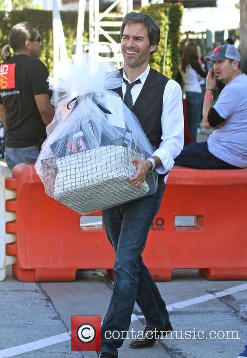 Eric McCormack holding a gift bag of electronic...