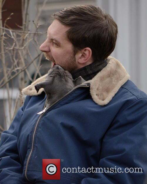Tom Hardy with an adorable puppy in his jacket while on set of Animal Rescue