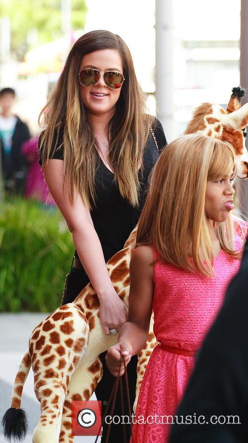 Khloe Kardashian holding a plush giraffe