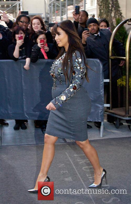 Pregnant Kim Kardashian departs her hotel wearing a beadazzled cotton dress