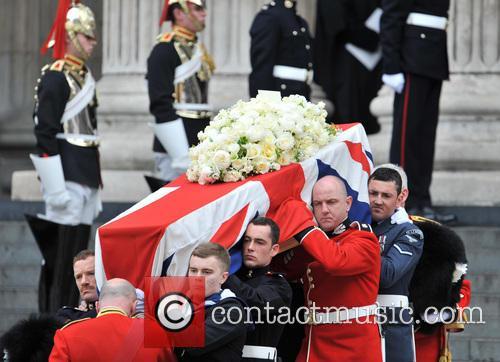 The funeral procession carrying the coffin of former...