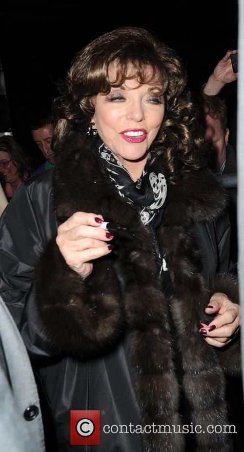 Joan Collins greets fans as she leaves the...