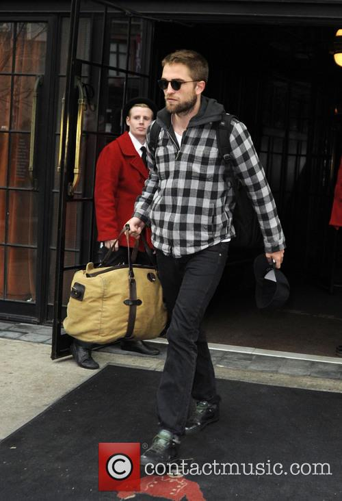 Robert Pattinson exits his hotel