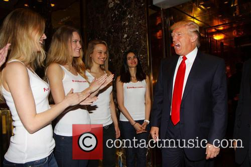 Donald Trump distributes free money at the launch of FundAnything.com at Trump Plaza.