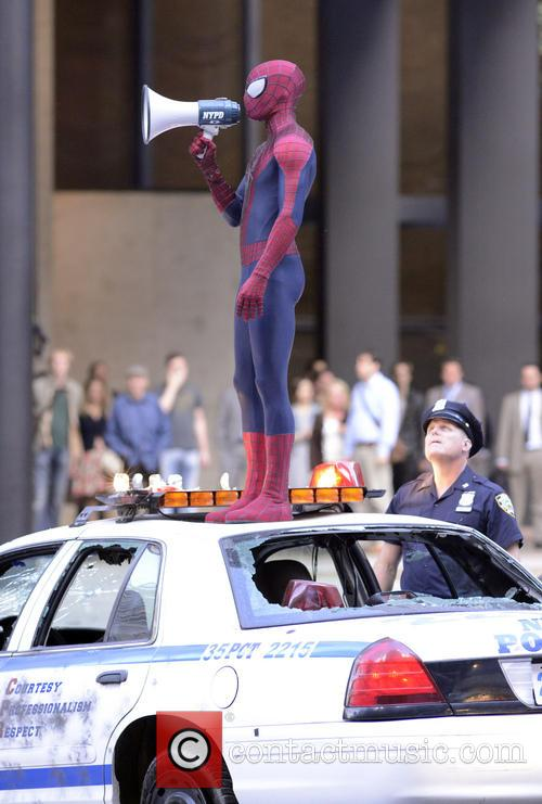 Spider Man addresses onlookers with a loud speaker